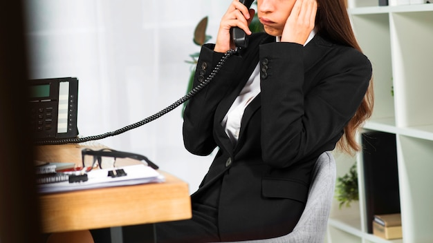 Upset young businesswoman talking on telephone