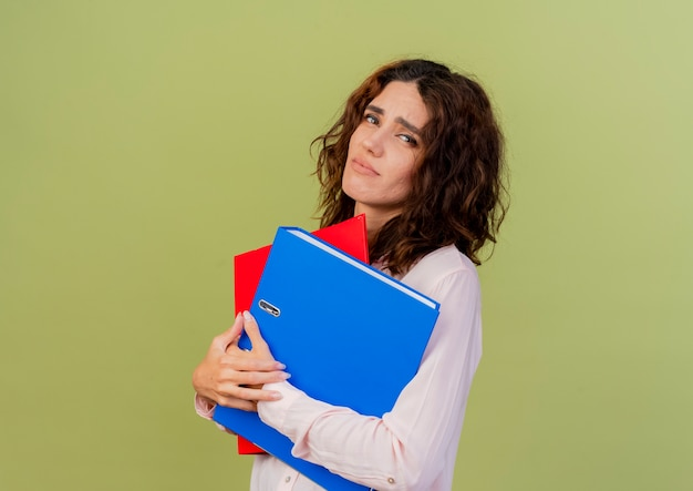 La giovane ragazza caucasica sconvolta tiene le cartelle di file che guarda l'obbiettivo isolato su priorità bassa verde con lo spazio della copia