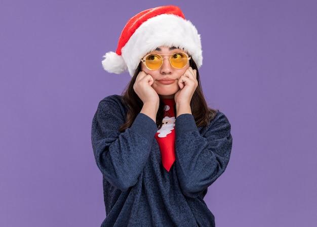 산타 모자와 산타 넥타이와 태양 안경에 화가 젊은 백인 여자 얼굴에 손을 놓고 측면에서 보인다