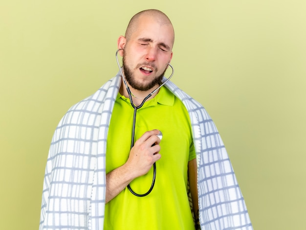 Расстроенный молодой кавказский больной, завернутый в плед, со стетоскопом, изолированным на оливково-зеленой стене с копией пространства