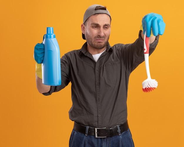 Sconvolto giovane uomo delle pulizie che indossa abiti casual e berretto in guanti di gomma tenendo la spazzola per la pulizia e la bottiglia con prodotti per la pulizia guardando la spazzola con espressione triste in piedi sopra la parete arancione