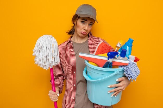 Sconvolto giovane donna delle pulizie in camicia a quadri e berretto che tiene secchio con strumenti per la pulizia e mocio che guarda l'obbiettivo con espressione triste che increspa le labbra in piedi su sfondo arancione