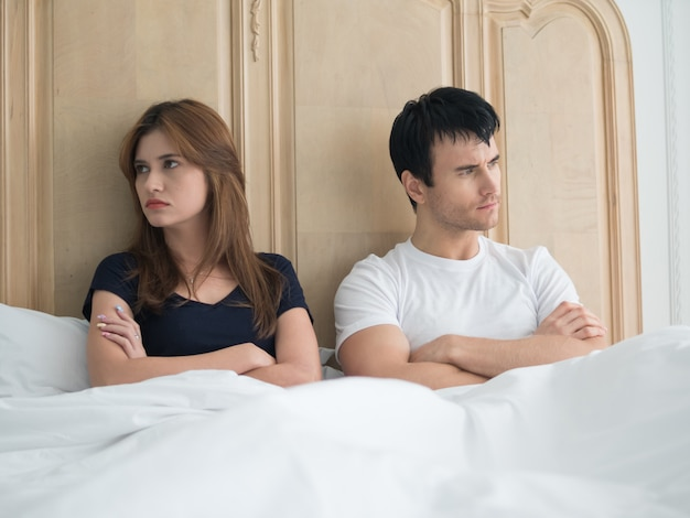 Upset young couple having problems in bedroom