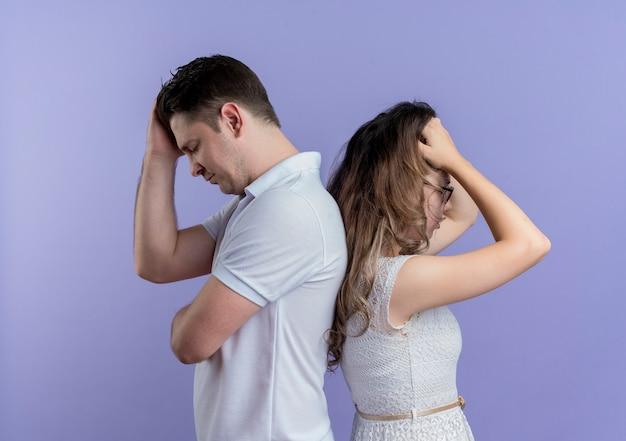 Sconvolto giovane coppia uomo e donna in piedi schiena contro schiena sul muro blu