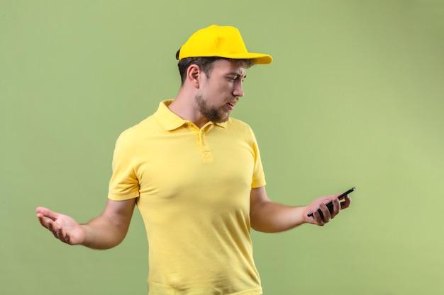 Sconvolto giovane uomo di consegna in maglietta polo gialla e berretto guardando lo schermo del suo smartphone diffondendo le mani cercando in piedi incerto e confuso sul verde isolato