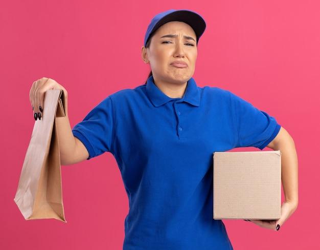 Sconvolto la giovane donna di consegna in uniforme blu e cappuccio che tiene il pacchetto di carta e la scatola di cartone guardando davanti con espressione triste in piedi sopra la parete rosa