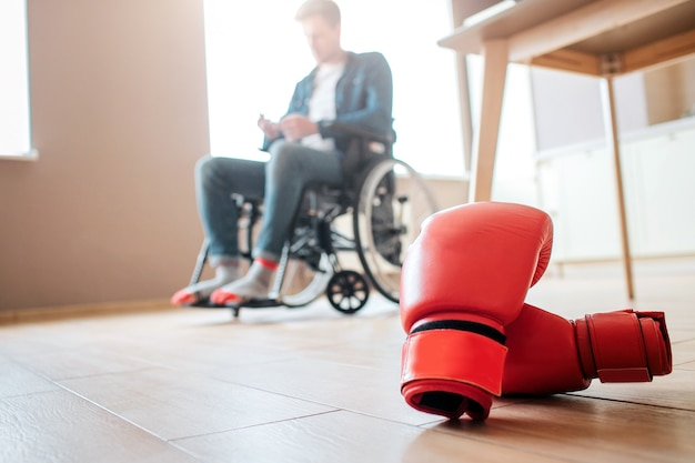 Upset young ex-sportsman with disability and inclusiveness sitting on wheelchair. boxer's gloves lying on floor.