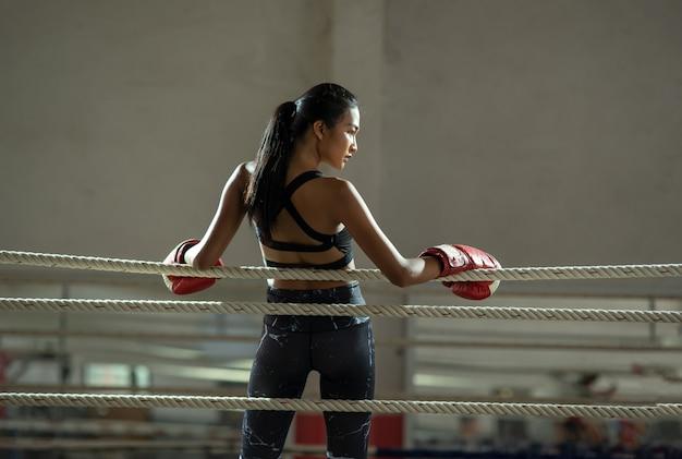 ジムでボクシンググローブを身に着けている動揺の若い戦闘機ボクサーの女の子、彼女の練習から休憩を取って女性ボクサー。