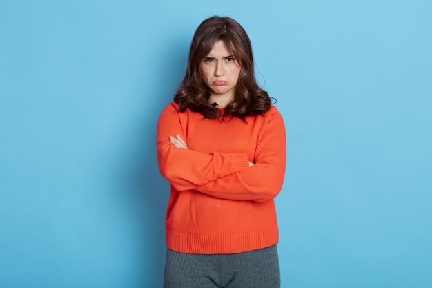 Расстроенная молодая девушка, стоящая над синим со сложенными руками