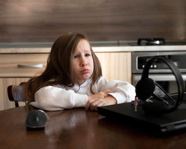 Upset young girl with laptop and headphones