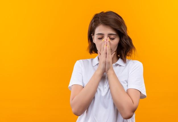 希望の表現で目を閉じて手をつないで白いポロシャツを着て短い髪の動揺した少女