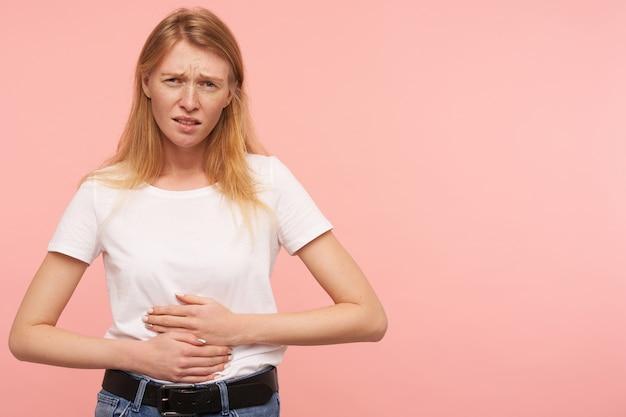 Sconvolto giovane donna dagli occhi verdi rossa vestita di maglietta bianca che tiene le mani sul suo ventre e sopracciglia accigliate mentre guarda la telecamera, isolato su sfondo rosa