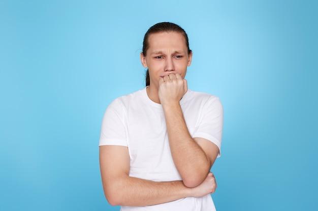 Tシャツを着た動揺した若い男は、何かを忘れたか、青い背景に孤立した間違いを犯しました。間違ったことを後悔している