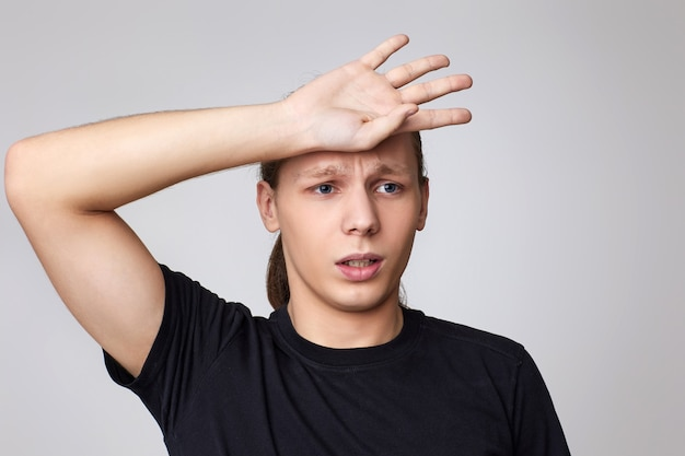 Upset young guy in t-shirt forgot something or made a mistake