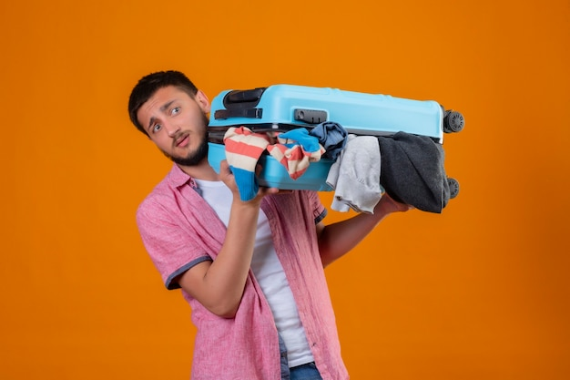 Upset young handsome traveler guy holding suitcase full of clothes looking aside with sad expression standing over orange background