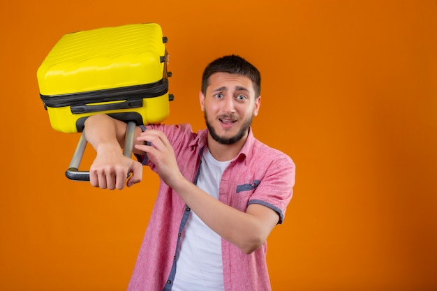 Upset young handsome traveler guy holding suitcase looking at camera with sad expression standing over orange background