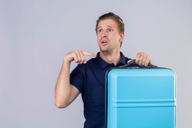 Upset young handsome traveler man holding suitcase looking away pointing finger to his suitcase standing over white background