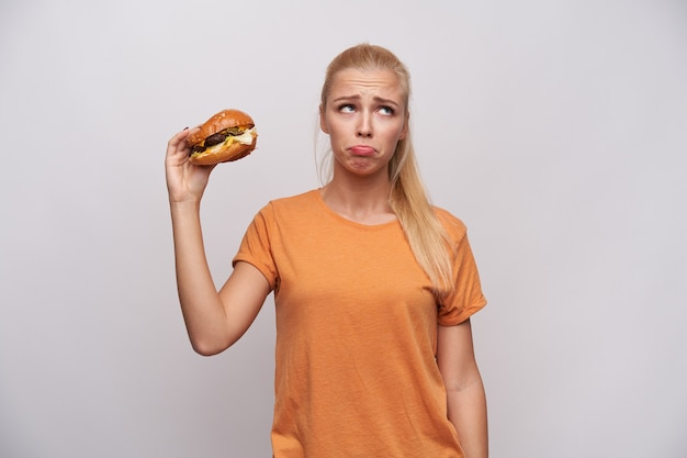 白い背景に立って、上げられた手で不健康な食べ物を保持しながら、悲しげに脇を見て額にしわを寄せるオレンジ色のtシャツで動揺した若い長い髪のブロンドの女性