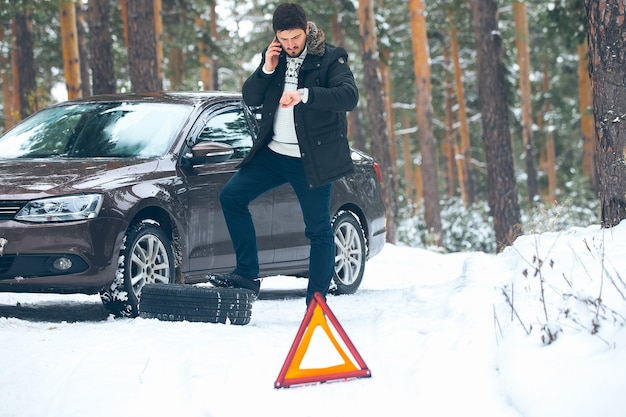 Upset young man calling the car service standing on the broken car in the winter in the woods.