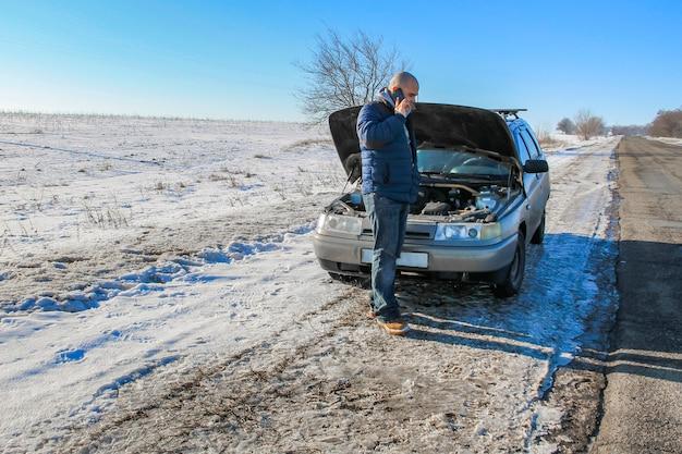 Расстроенный молодой человек звонит в автосервис, стоя возле разбитой машины на зимней дороге