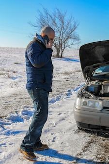 겨울 도로에서 부서진 차 근처에 서 있는 자동차 서비스에 전화하는 화가 난 청년
