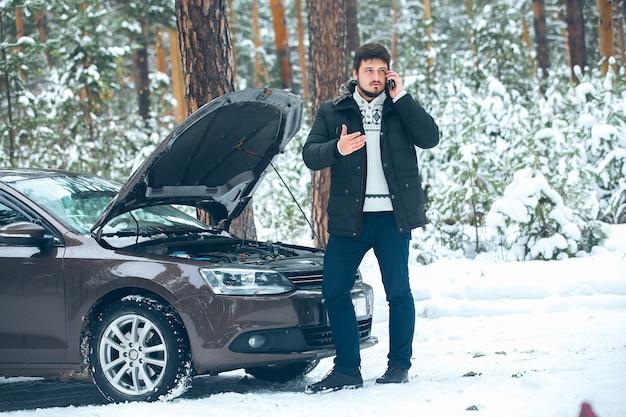 Расстроенный молодой человек звонит в автосервис, стоя на разбитой машине зимой в лесу. машина помощи на дороге
