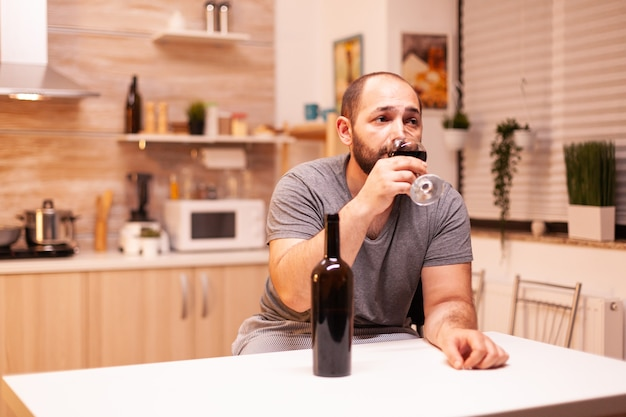 Upset young man drinking alone a bottle of red wine sitting at table in kitchen. unhappy person disease and anxiety feeling exhausted with having alcoholism problems.
