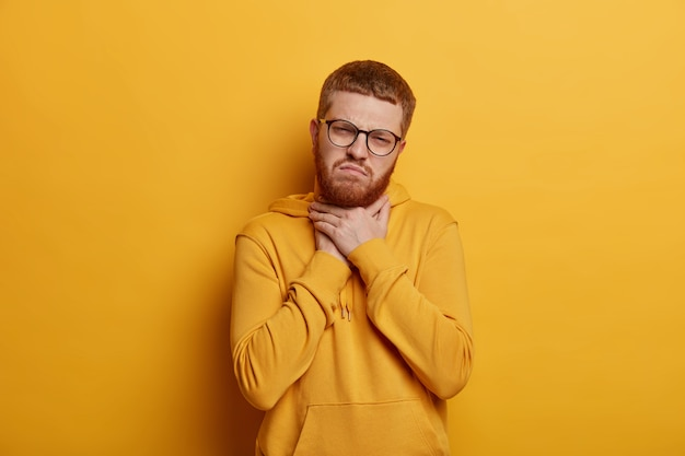 Upset young man has short ginger hair and bristle, touches neck and suffers from sore throat, has painful feeling while swallowing, wears hoodie, isolated over yellow wall. bad symptom
