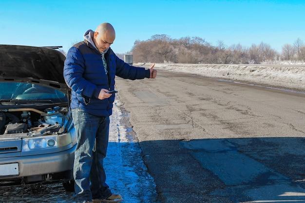 Расстроенный молодой человек, путешествующий автостопом и набирающий номер для помощи, стоит возле разбитой машины на зимней обочине дороги