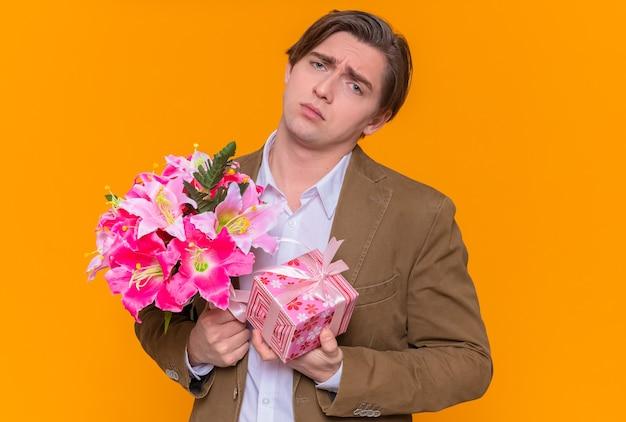 오렌지 벽 위에 서있는 국제 여성의 날을 축하하려고 슬픈 표정으로 정면을 바라 보는 꽃의 꽃다발과 현재를 들고 화가 젊은 남자
