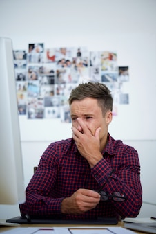 Upset young man looking at computer screen, covering face with hand and crying