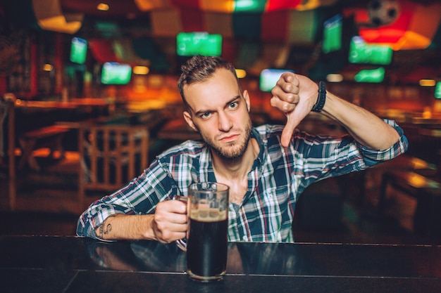 Upset young man sit at bar counter in pub and look . he hold big thumb down. guy has mug of dark beer.