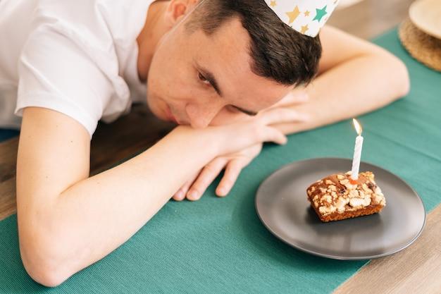 Расстроенный молодой человек сидит на именинном торте и смотрит в сторону. концепция одиночества в карантине во время пандемии коронавируса covid-19.