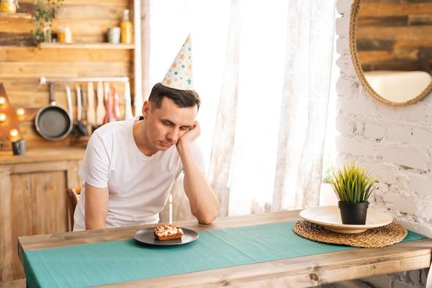 Расстроенный молодой человек сидит на именинном торте и смотрит на него грустными глазами. концепция празднования в одиночку.