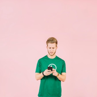 Upset young man using mobile phone over pink background