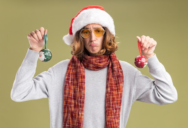 クリスマスのサンタの帽子と彼の首の周りに暖かいスカーフと黄色のメガネを身に着けている若い男は、緑の背景の上に立っている唇をすぼめる悲しい表情でカメラを見てクリスマスボールを保持しています