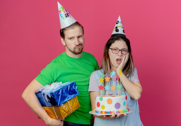 Upset young man wearing party hat holds gift boxes standing with displeased young girl wearing party hat puts hand on face holding birthday cake isolated on pink wall