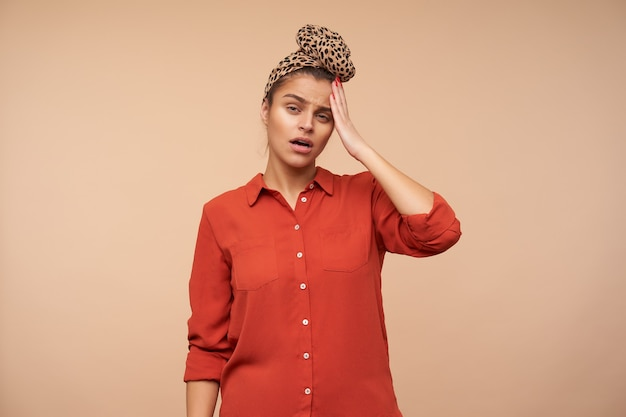 Upset young pretty brown haired woman with headband squinting her eyes and keeping raised palm on forehead while standing over beige wall in casual clothes