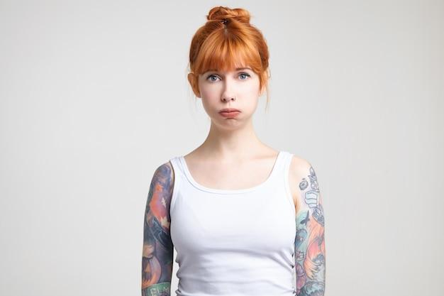 Sconvolto giovane signora tatuata piuttosto rossa con trucco naturale gonfiando le guance mentre guarda stancamente la fotocamera, in piedi su sfondo bianco
