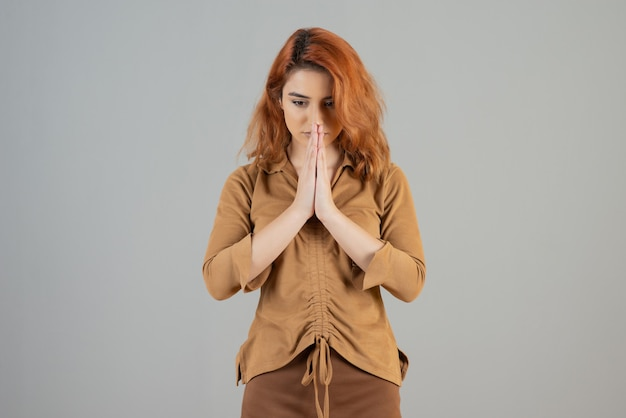 An upset young redhead praying on grey wall