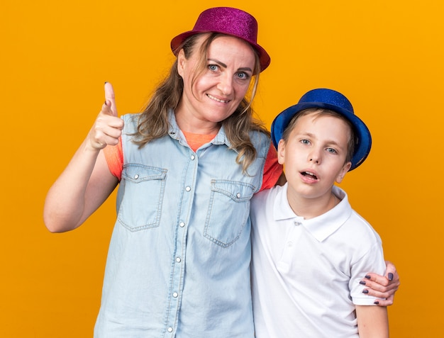 Upset young slavic boy with blue party hat standing with his mother wearing purple party hat and pointing at side isolated on orange wall with copy space