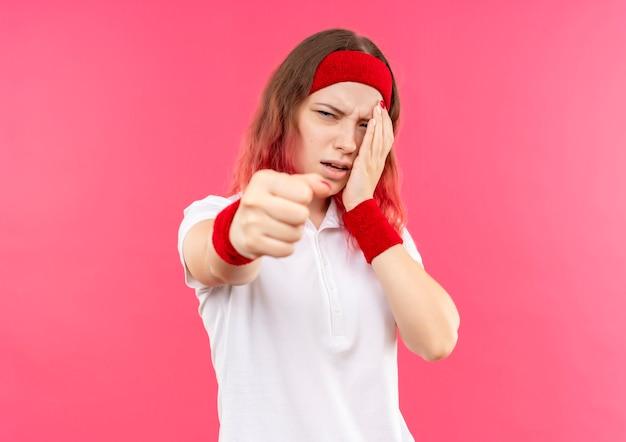 Sconvolto giovane donna sportiva in fascia che tocca il suo occhio che mostra il pugno alla telecamera con la faccia infelice in piedi sopra la parete rosa