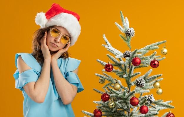 Sconvolto giovane donna in top blu e cappello da babbo natale che indossa occhiali gialli con espressione triste in piedi accanto a un albero di natale su muro arancione