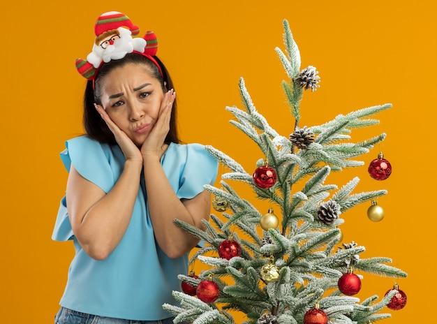 Sconvolto giovane donna nella parte superiore blu indossando divertenti natale cerchio sulla testa guardando la fotocamera con espressione triste in piedi accanto a un albero di natale su sfondo arancione