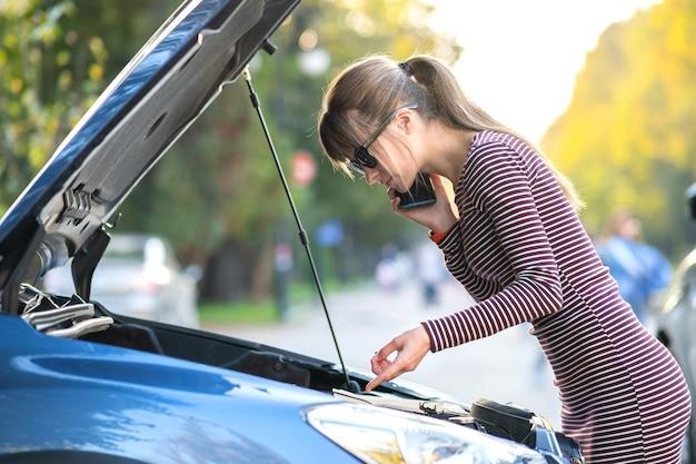 Расстроенная молодая женщина-водитель сердито разговаривает по мобильному телефону со службой помощи возле разбитой машины с открытым капотом на городской улице.