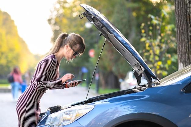 Расстроенная молодая женщина-водитель сердито разговаривает по мобильному телефону со службой помощи возле разбитой машины