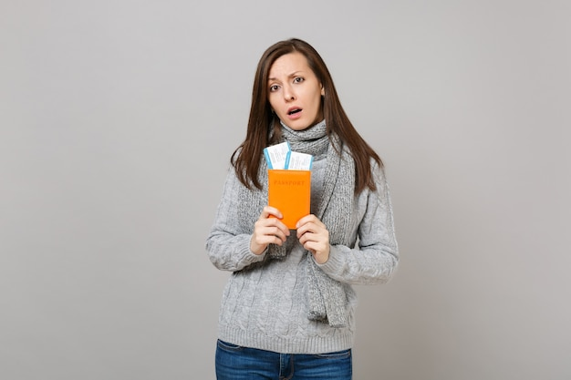 Upset young woman in gray sweater, scarf holding passport, boarding pass ticket isolated on grey background. healthy fashion lifestyle people sincere emotions, cold season concept. mock up copy space.
