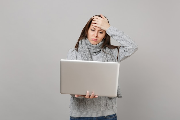 Upset young woman in gray sweater, scarf putting hand on forehead, working on laptop pc computer isolated on grey wall background. healthy lifestyle, online treatment consulting, cold season concept.