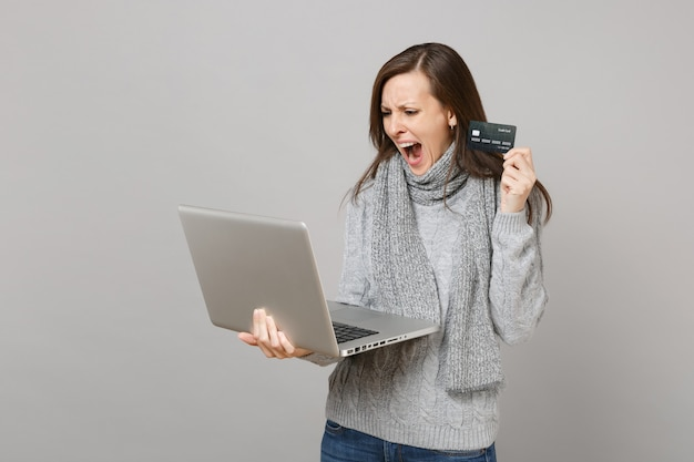 Upset young woman in gray sweater, scarf screaming working on laptop pc computer hold credit bank card isolated on grey background. healthy lifestyle, online treatment consulting, cold season concept.