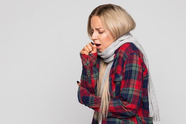 Расстроенная молодая женщина в клетчатой рубашке, закутанная в шарф, кашляет